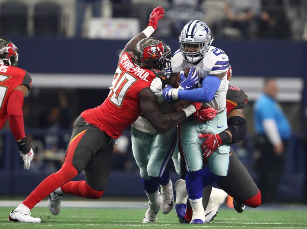 Dec 23, 2018; Arlington, TX, USA; Dallas Cowboys running back Ezekiel Elliott (21) runs with the ball in the second quarter against Tampa Bay Buccaneers defensive end Jason Pierre-Paul (90) at AT&T Stadium. Mandatory Credit: Matthew Emmons-USA TODAY Sports