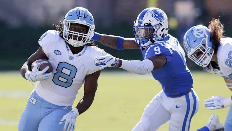 UNC Football's Michael Carter (8) runs while Duke's Jeremy McDuffie (9) reaches for the tackle during the first half of an NCAA college football game in Durham, N.C., Saturday, Nov. 10, 2018. (AP Photo/Gerry Broome)